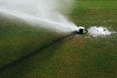 Golf course automatic lawn sprinkler. In action Stock Photos