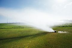 Golf course automatic lawn sprinkler. In action Stock Photography