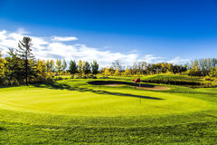 Golf Course in Autumn. The fall colors of autumn surround the greens of the golf course Royalty Free Stock Images