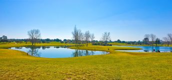 Golf Course, Beautiful Landscape Scenery, Bright Blue Sky, Sunny Day, Small Lakes and Trees Royalty Free Stock Images