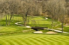 Golf course bridge scene. A scene on a golf course in Peoria, Illinois. A golf cart pathway leading to a bridge and than vanishing into the distance royalty free stock photography