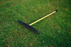 Golf course bunker rake on green grass. Closeup view Royalty Free Stock Image