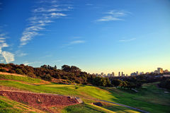 Golf course with city skyline in the distance Stock Photo