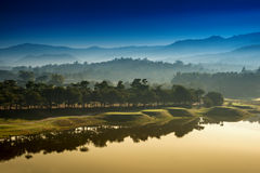 Golf course at dawn backlit by rising sun Royalty Free Stock Image