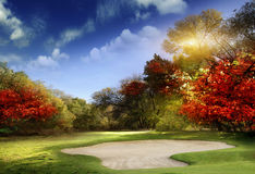 Golf course at dawn backlit by rising sun. Autumn Foliage at the Golf Course - The sun shines on a putting green and lake at a golf course in Autumn Stock Images