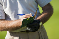 Golf course detail. Player writing the results in his notebook Stock Photo