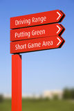 Golf course direction signs. A red pole with sign arrows, pointing directions in a golf course: Driving Range, Putting Green, Short Game Area, over a clear blue Stock Photo