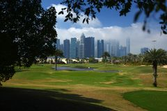 The golf course in dubai. Golf course in Dubai with palm trees and skyscrapers in the background royalty free stock photography