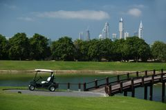 Golf course in Dubai with palm trees and skyscrapers in the background. Golf course with golfcart, trees and skyscrapers in the background royalty free stock photos