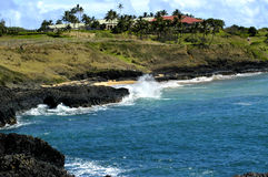 Golf Course on Edge of Ocean. Kauai Lagoons golf course sits on the top of a cliff overlooking the pacific ocean.  waves crash and blue waters, and black cliffs Royalty Free Stock Images