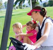 Golf course family mother and daughters in buggy. Green grass field Stock Photography
