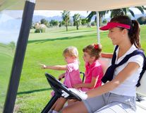 Golf course family mother and daughters in buggy. Green grass field Stock Image