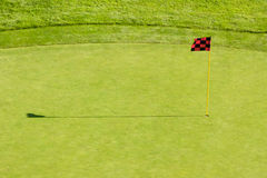 Golf Course Flag. A red and black checkered golf course flagstick on a putting green Royalty Free Stock Photography