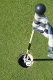 Golf Course Flag And Two Golf Balls. Close up of a golf course flag and two golf balls Stock Photos
