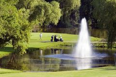 Golf Course Fountain And Golfers. As nice a view that this is ... it is a hazard for the golfers. Autumn in Wisconsin. The ball will go over or in the pond Stock Photos