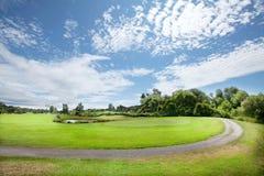 Golf course green. Gravel road through golf course. On green with flag Stock Photos