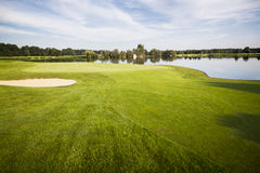 Golf course with green. Golf course with green, sand trap and lake with cloudscape in background stock photography