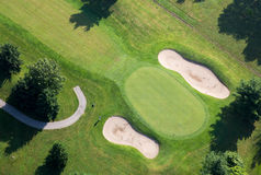Golf Course Green Aerial Photo. Aerial photography of golf course putting green, sand traps and golfer ready to chip onto green royalty free stock images