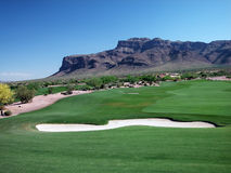 Golf Course Green Belt with Bunker and Mountains. A green belt at a golf course bordered by the majestic Superstition Mountains in Arizona Royalty Free Stock Photos