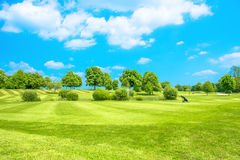 Golf course. Green field with fresh grass and blue sky Royalty Free Stock Images