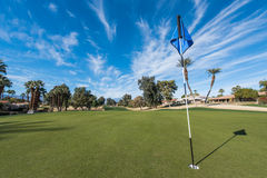 Golf course green with flag in hole Royalty Free Stock Image