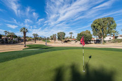 Golf course green with flag in hole Stock Photo