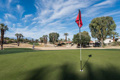 Golf course green with flag in hole Royalty Free Stock Photo