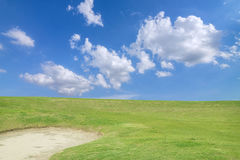 golf course - green golf field and sand pit with sky blue cloud Royalty Free Stock Photography