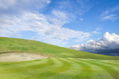 golf course - green golf field and sand pit with sky blue cloud Royalty Free Stock Photo