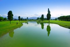 Golf course green grass field lake reflection. Golf course green grass field lake trees reflection Royalty Free Stock Images