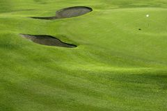 Golf course green grass hill field with holes Stock Image