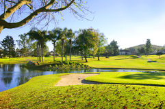 Golf course with green grass, sand bunker and pond Royalty Free Stock Images