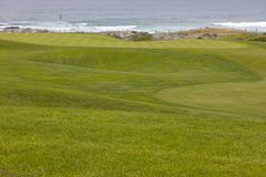 Golf course greens leading to hole by the ocean Royalty Free Stock Photo