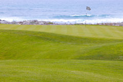 Golf course greens leading to hole by the ocean. Beautiful, manicured golf course greens on a softly rolling hilly topography leading to the hole. The putting stock photo
