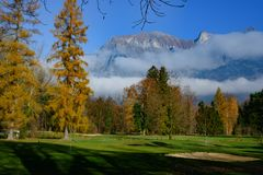 Golf course `Heidiland` Bad Ragaz, Switzerland. Golf course with bunker and fairway in autumn with fog in front of Alps, Bad Ragaz royalty free stock photo