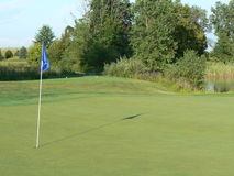 Golf Course Hole. Golf Course blue flagged hole on a beautiful day Royalty Free Stock Images