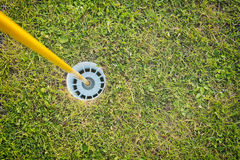 Golf Course Hole with Yellow Pole Royalty Free Stock Photos
