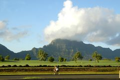 Golf Course on Kauai, Hawaii. Beautiful mountain backdrop for golf course on Kauai, Hawaii.  Road runs across front of landscape with a man riding a bike Royalty Free Stock Image