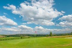 Golf course landscape Golf field green grass red flag blue sky Stock Photos