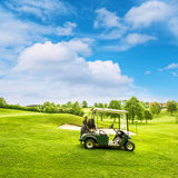 Golf course lanscape with a cart over blue sky Stock Photos