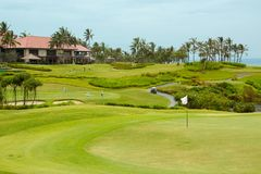 Golf course in luxury resort. Green field and blue sky Stock Photos