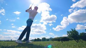 Golf course with a man strongly striking the ball