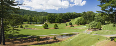 Golf course in mountain terrain pano Stock Image
