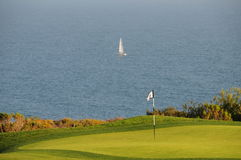 Golf course near the water. A golf course hole close to the water with a sailboat in the distance Stock Image
