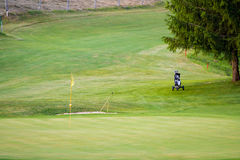 Golf course with one flag pole and trolley on fairway Stock Photos