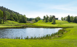 Golf course with pond, blue sky and green nature. Golf course with green and pond, green and blue colors Royalty Free Stock Photos
