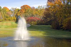Golf Course Pond And Fountain. As nice a view that this is ... it is a hazard for the golfers. Autumn in Wisconsin. The pond is also a used to water the golf Royalty Free Stock Image