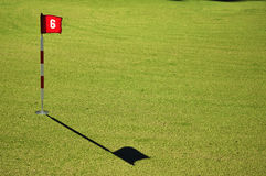 Golf Course Practice Green. Flag and Flagstick with Shadow on a Golf Course Practice Green Royalty Free Stock Photos