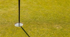 Golf Course putting green hole with flag pole royalty free stock photo