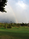 Golf course with rainbow. A beautiful golf course, impeccable lawn, with rainbow and dramatic clouds Stock Photo